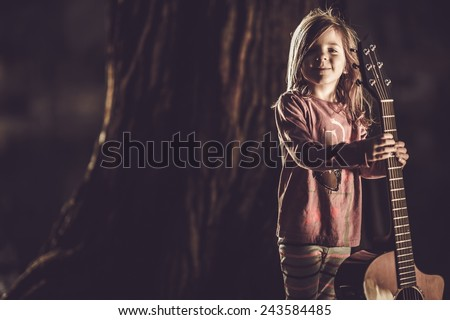 Cute Little Girl with Acoustic Guitar in the Park. Acoustic Guitar Little Player. Music Concept. - stock photo