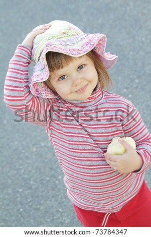 Cute little girl with an apple outdoors - stock photo