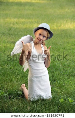 Cute little girl with angel wings shows thumbs up sitting on the green lawn