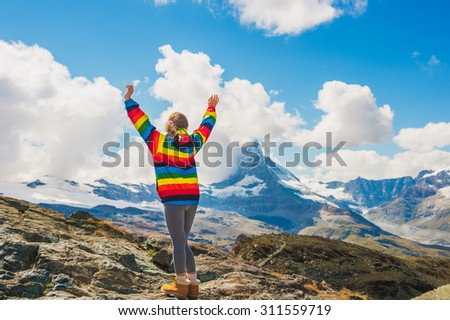 Cute little girl with arms wide open, wearing colorful coat, standing in front of Matterhorn mountain, Switzerland, back view - stock photo