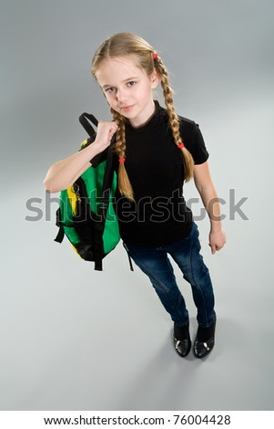 Cute little girl with backpack, from top viewpoint - stock photo