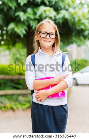 Cute little girl with backpack, holding a pink notebook, outdoor portrait, wearing white top and black skirt - stock photo
