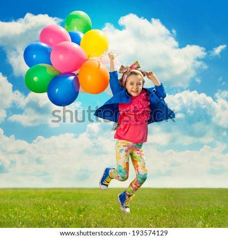 Cute little girl with balloons jumping on the green field. Happiness, fashionable concept. - stock photo
