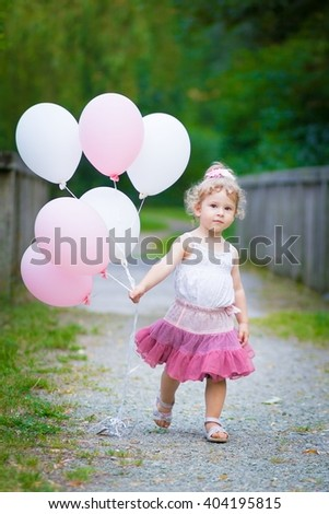 cute Little Girl with balloons walking in the park