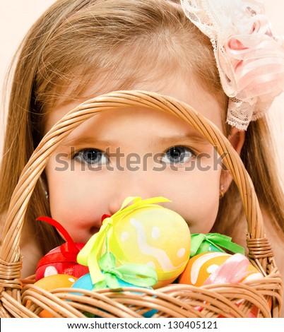 Cute little girl with basket full of colorful easter eggs - stock photo