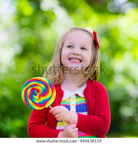Cute little girl with big colorful lollipop. Child eating sweet candy bar. Sweets for young kids. Summer outdoor fun. Preschooler kid with sugar lolly. Children having snack in a park after preschool. - stock photo