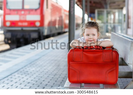 Cute little girl with big red suitcase on a railway station. Kid waiting for train and happy about a journey. - stock photo