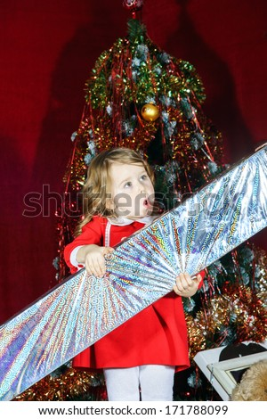 Cute little girl with big sweet christmas gift near conifer tree