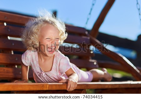Cute little girl with blond curly hair playing on wooden chain swing - stock photo