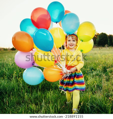 cute little girl with colorful balloons in field - stock photo