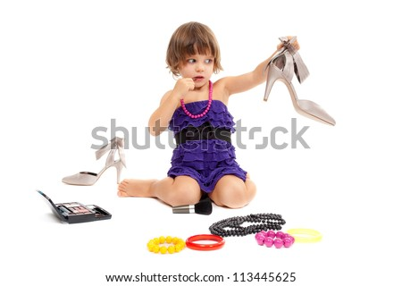Cute little girl with cosmetics and women's shoes in the studio. Isolate on white.