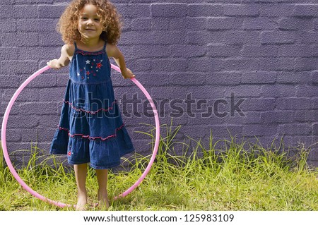 Cute little girl with curly hair posing with her hula hoop in front of a blue brick wall - stock photo