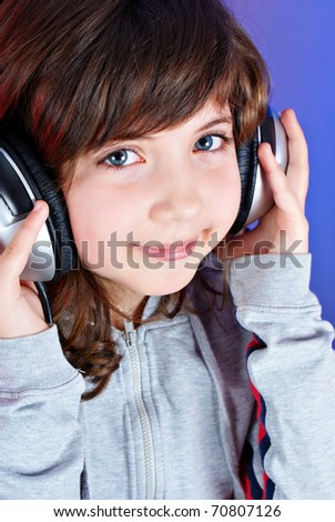 Cute little girl with earphones isolated on blue - stock photo