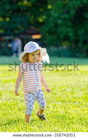 Cute little girl with fancy hat walking in the grass in summer time - stock photo