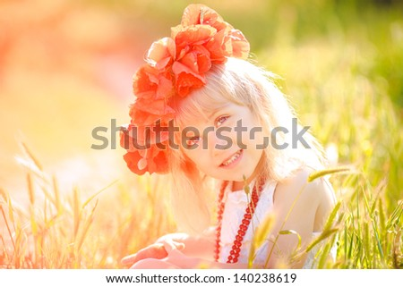 Cute little girl with flower garland in the poppy field at sunset