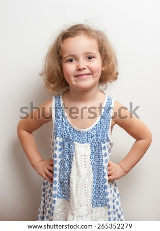 Cute little girl with funny ringlets (curly hair) in white and blue clothes looking very happy. She smiles, holds hands on the clothes and looks ahead on a background white wall, studio portrait. - stock photo