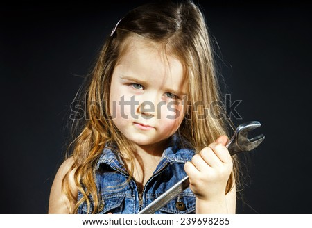 Cute little girl with gas spanner in her hands ready to professional constructing work - stock photo