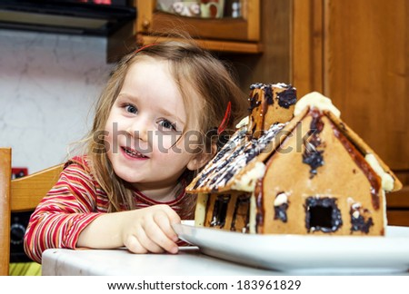 Cute little girl with gingerbread house at the kitchen - stock photo