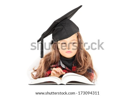 Cute little girl with graduation hat reading a book isolated on white background