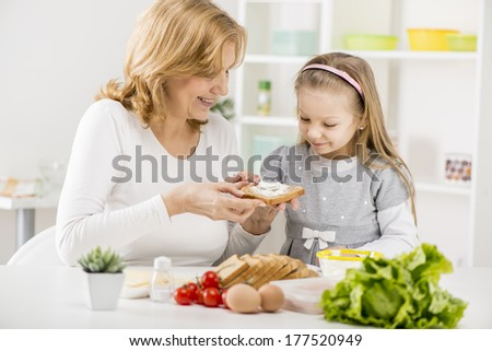 Cute little girl with Grandmother making a Sandwich in the kitchen. - stock photo
