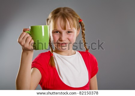 Cute little girl with green mug - stock photo