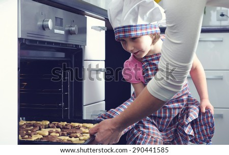 Cute little girl with her mother baking cookies in oven at home