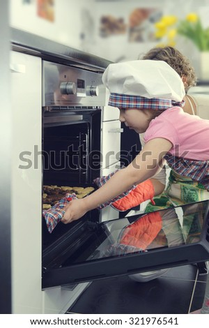 Cute little girl with her mother baking cookies in oven at home - stock photo