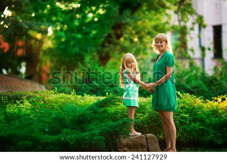 cute little girl with her mother in the park - stock photo