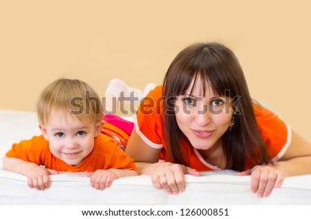 Cute little girl with her mother lying on a bed - stock photo