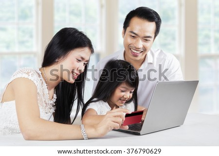 Cute little girl with her parents using laptop and credit card for shopping online at home - stock photo