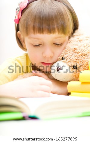 Cute little girl with her toy bear are reading a book while sitting at table - stock photo