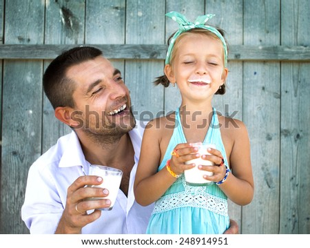 Cute little girl with his father holding glasses of milk over wooden background - stock photo