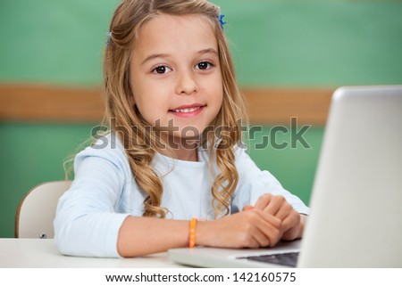 Cute little girl with laptop at classroom desk - stock photo