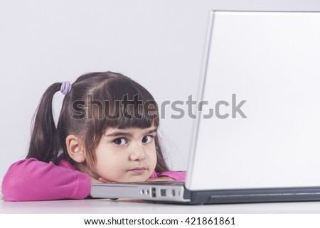 Cute little girl with laptop computer. Education, technology and e-learning concept