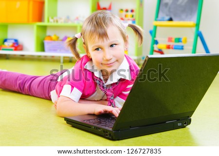 Cute little girl with laptop lying on floor
