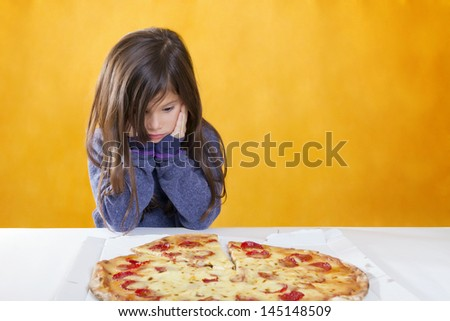 Cute little girl with long hair has blue sweater is expectant in front of a pizza - stock photo
