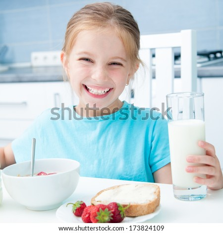 cute little girl with milk  eating cereal and strawberries in the white kitchen - stock photo