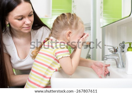 Cute little girl with mom washing face in bathroom - stock photo