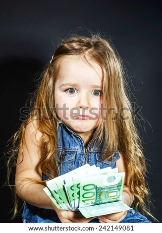 Cute little girl with money euro in her hand. Business concept. How much it costs to be happy. - stock photo