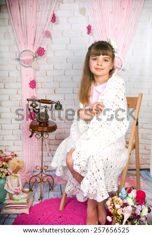 Cute little girl with old phone wrapped in a delicate blanket sitting on a wooden studio in the scenery