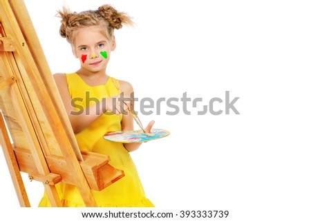 Cute little girl with painted colorful face drawing on easel. Happy childhood. Isolated over white. - stock photo