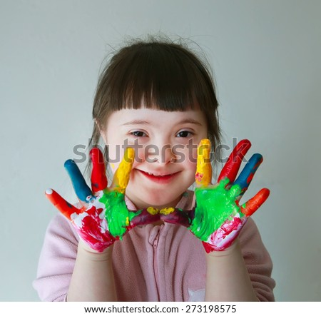 Cute little girl with painted hands. Isolated on grey background. - stock photo