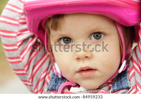 Cute little girl with pink bicycle helmet - stock photo