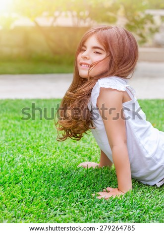 Cute little girl with pleasure doing push-ups outdoors, exercising on fresh green spring field in sunny day, health lifestyle, active childhood concept - stock photo