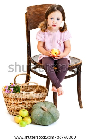 Cute little girl with ponytails eating apple. Isolated on white