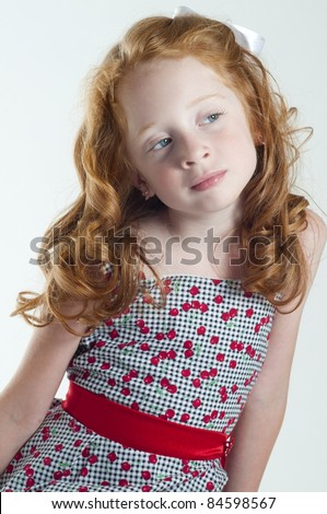 Cute little girl with red hair thinking