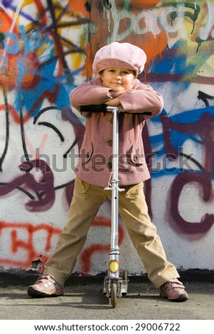 Cute little girl with scooter takes a respite near graffiti painted wall - stock photo