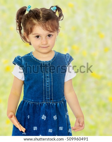 Cute little girl with short pigtails on the head, in a blue dress with short sleeves. Close-up.Summer white green blurred background.