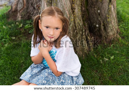 Cute little girl with sweet pigtails sitting under the tree, holding a diary