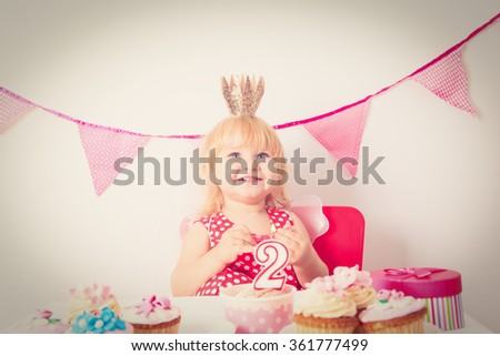 cute little girl with sweets at birthday party - stock photo